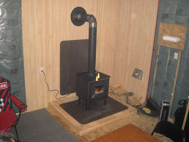 Here is another picture of the woodstove installed with the platform i was  required to sit - 16x16 Hunting Cabin - Small Cabin Forum (1)