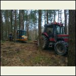 Tractor moving logs